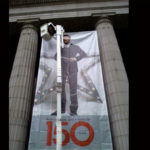 large banner outside between two columns showing male model and 150 years