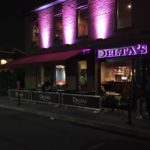 exterior of Delta's with sidewalk barrier with graphic and backlit sign