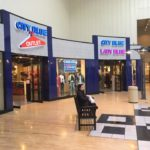Indoor Shopping mall store front with signs that say City Blue Outlet and City Blue Lady Blue