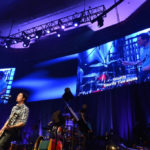 2 large digital displays behind stage with singer and band on stage