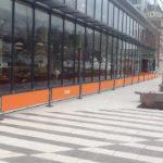 orange sidewalk barriers outside restaurant