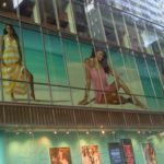 large window graphics of women in clothing in second floor store window on city street