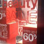 """Window lettering """"beauty sale"""" in red on store window"""